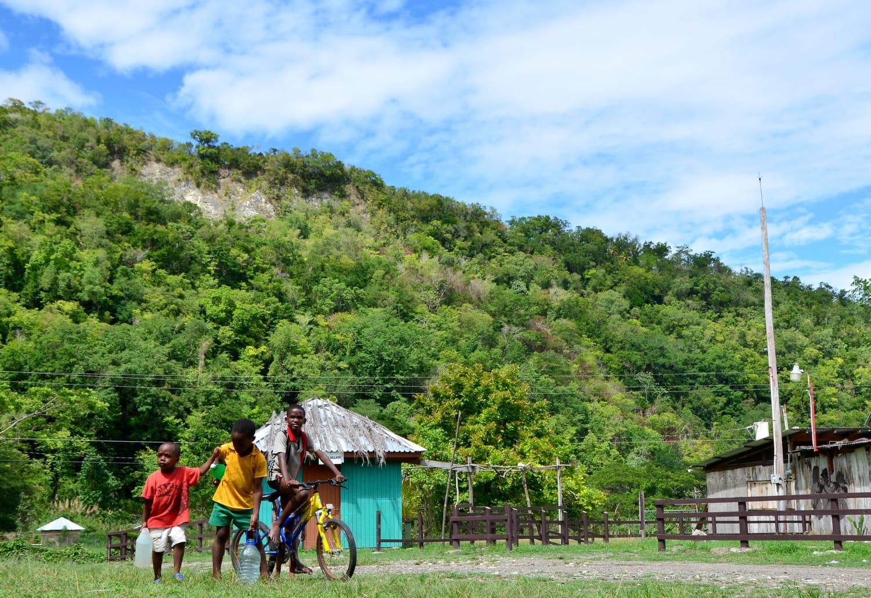 Drei Kinder auf Fahrrädern in einem Dorf auf Jamaika
