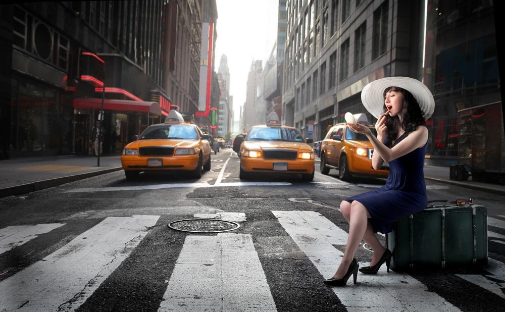 Extravagante Lady auf Koffer sitzend auf Zebrastreifen