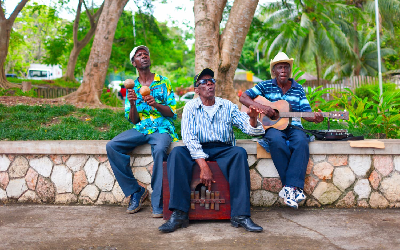 Drei singende jamaikanische Männer auf einer Parkmauer