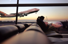 Zwischenstopp: Frau am Flughafen am Gate wartend