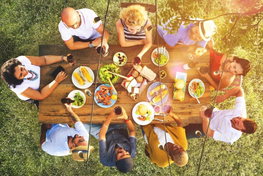 Mehrere Personen sitzen draußen an einem Tisch
