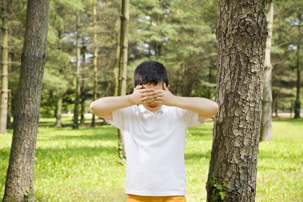 Versteckspiel: Junge im Wald