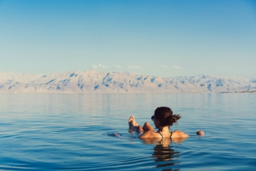 Frau schwimmt auf Wasseroberfläche auf dem Toten Meer in Jordanien