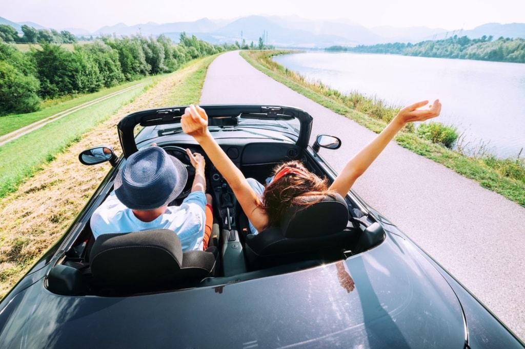 Mann und Frau fahren im Cabrio parallel zu einem Fluss