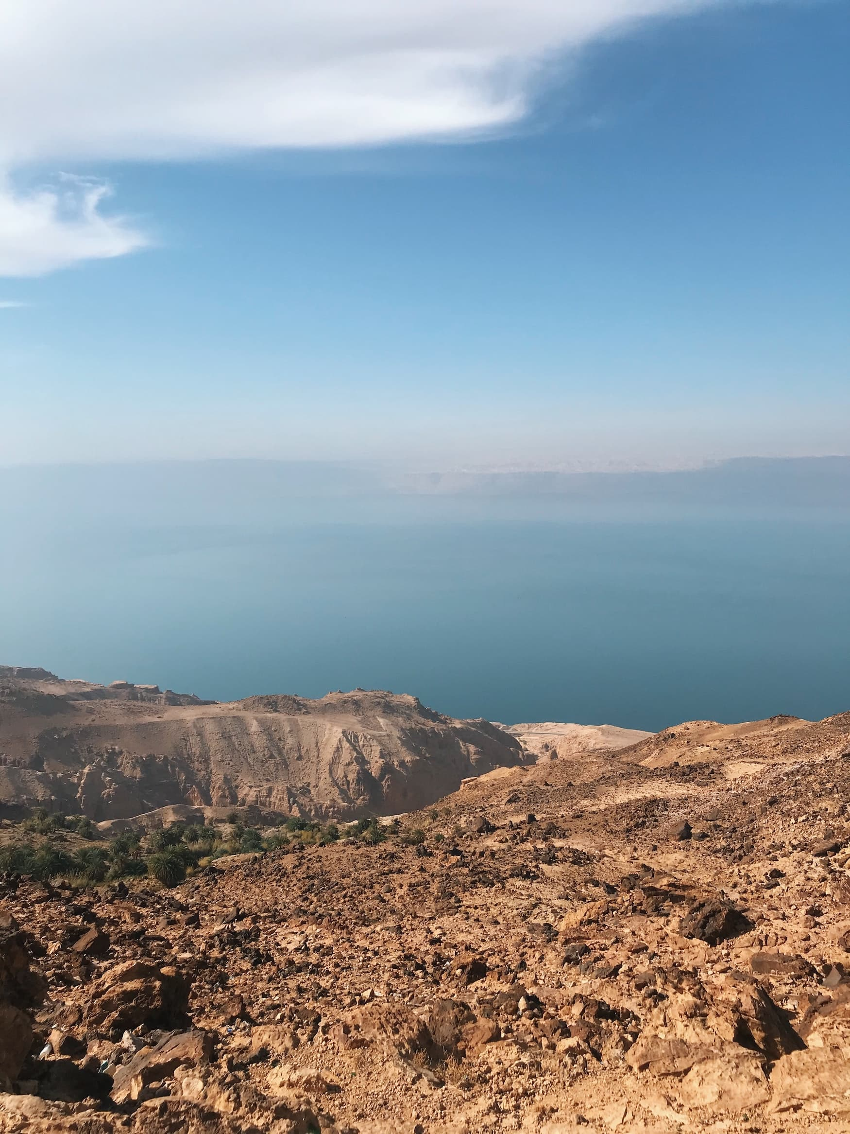 Im Vordergrund ine trockene, schroffe Landschaft und im Hintergrund kann man das türkisfarbene Wasser des Toten Meers erahnen