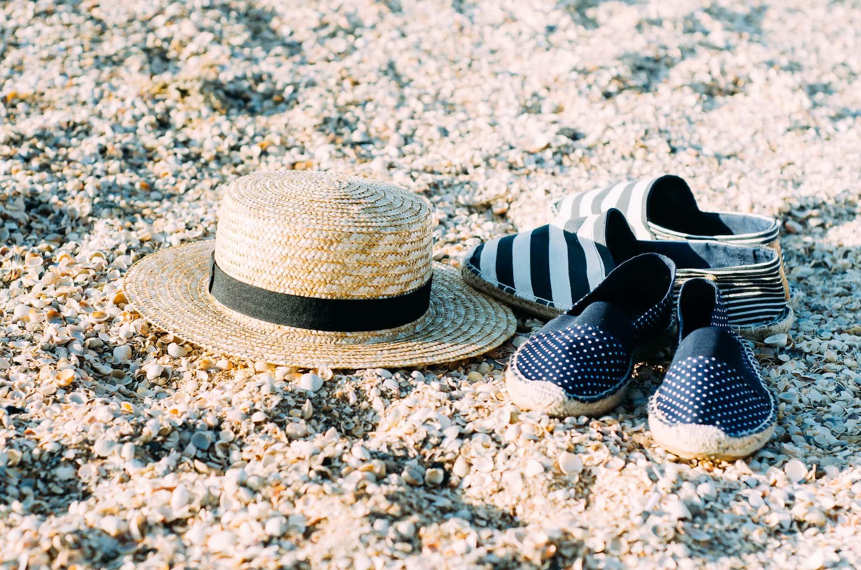 Espadrilles und Strohhut liegen auf Sand an Strand in Frankreich