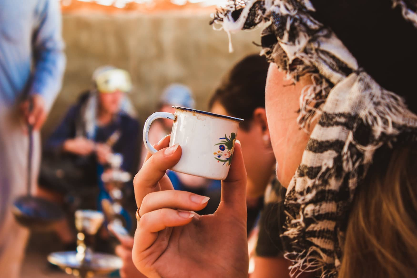 Touristin trinkt Ingwer-Tee aus einer Emaille-Tasse im Wadi el Gemal Nationalpark