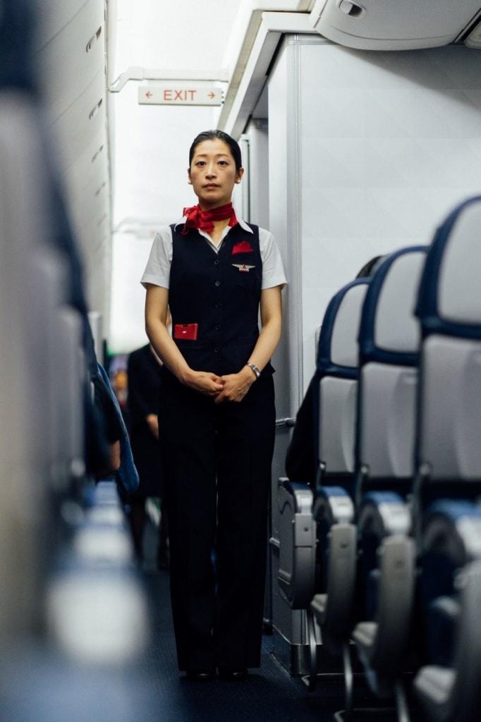 Flugbegleiterin steht im Gang