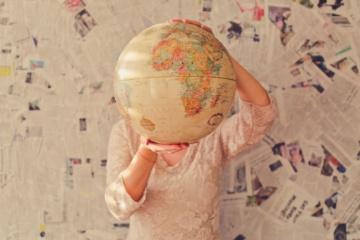 Frau hält sich Globus vor Gesicht
