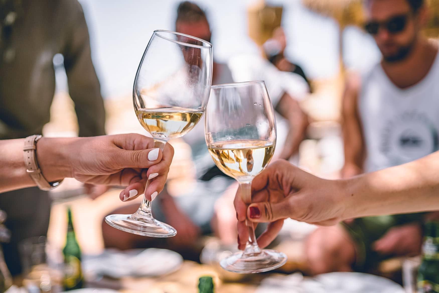 zwei Weißweingläser stoßen bei einem Picknick an