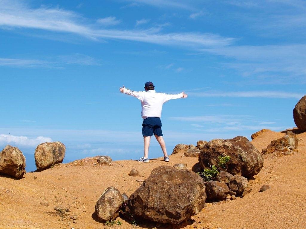 Steine am Strand und ein Mann der die Arme ausbreitet auf Lanai