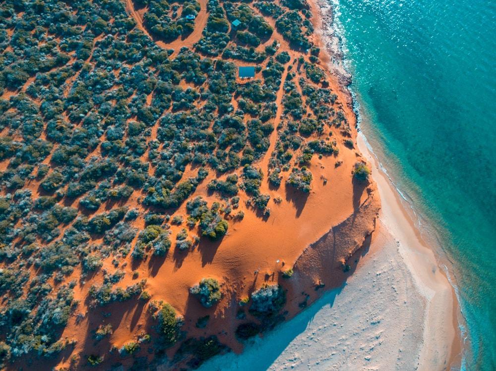Küstenabschnitt mit weißem Strand und roten Klippen