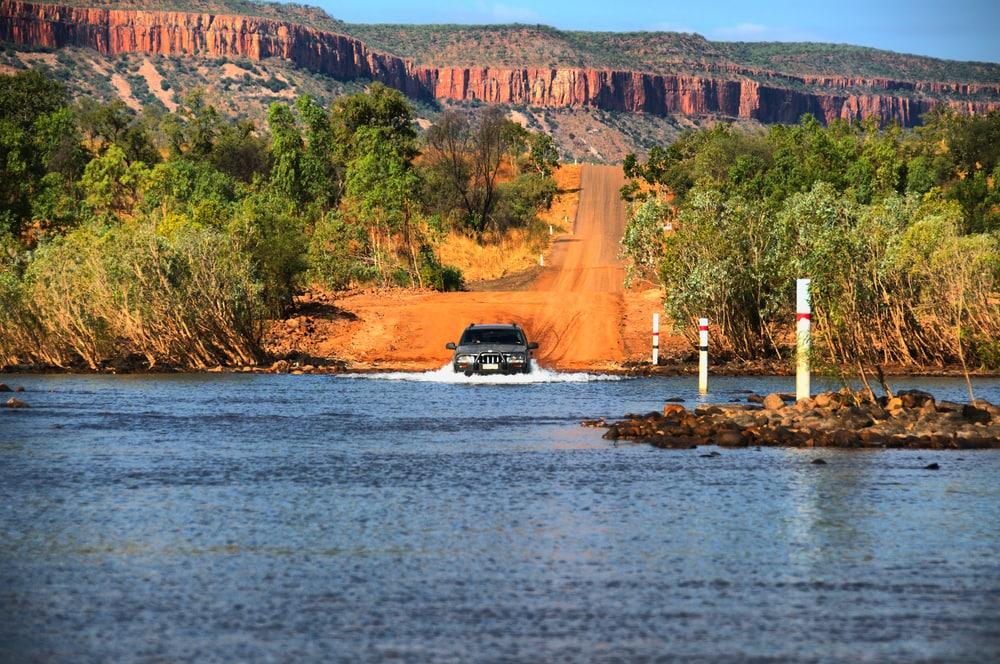 Auto fährt durch überschwämmte Straße in Outback