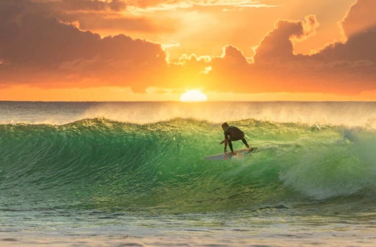 Surfer reitet die perfekte Welle im Sonnenuntergang.