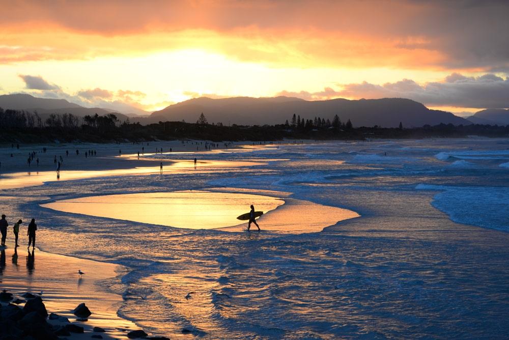 Weitläufiger Strand im Sonnenuntergang mit Surfern