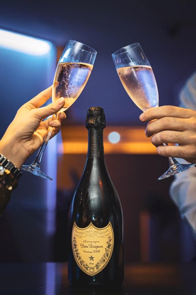 Mann und Frau stoßen mit Champagner-Gläsern an
