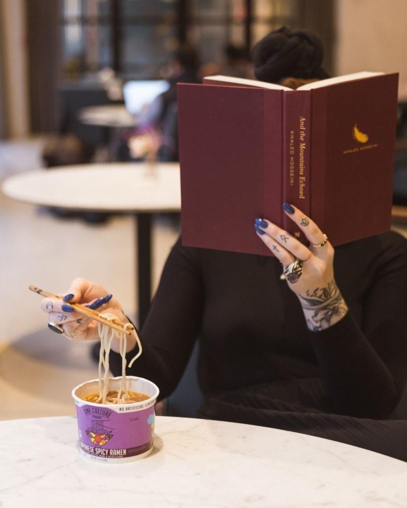 Frau hinter Buch sitzt am Tisch, liest und isst Instantnudelsuppe