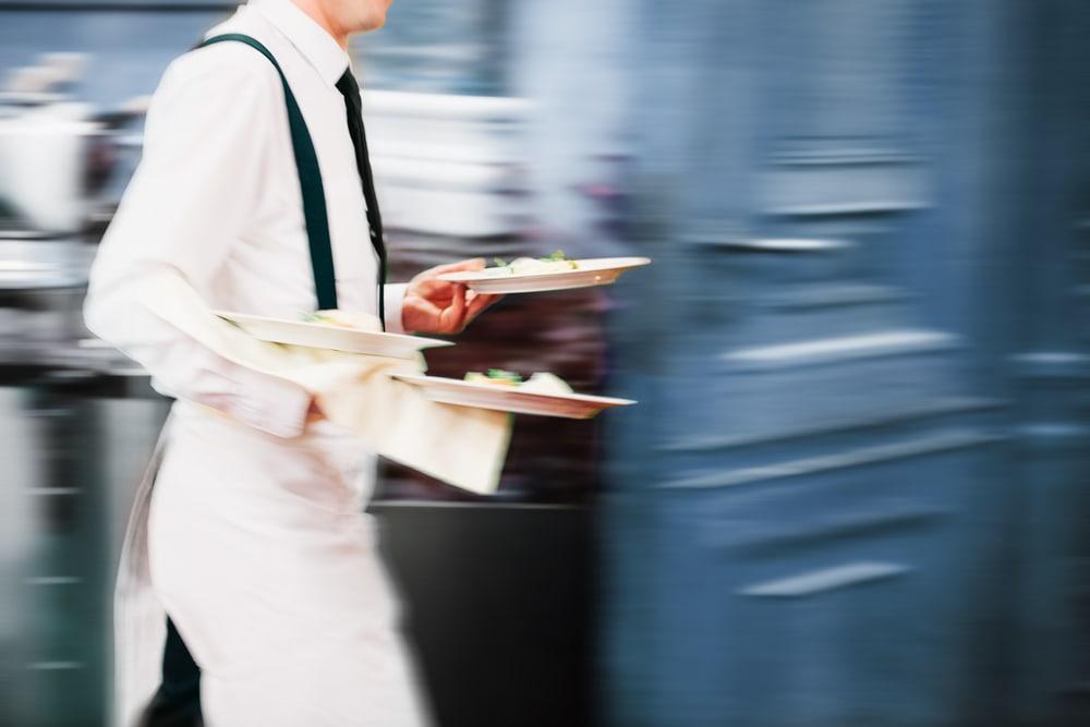 Kellner im Restaurant im Tellern in der Hand