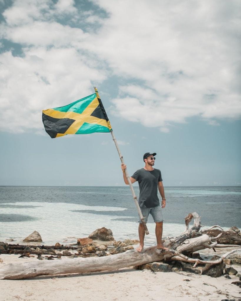 Mann am Strand mit Flagge Jamaikas