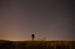 Mann mit Fahrrad blickt in Sternenhimmel
