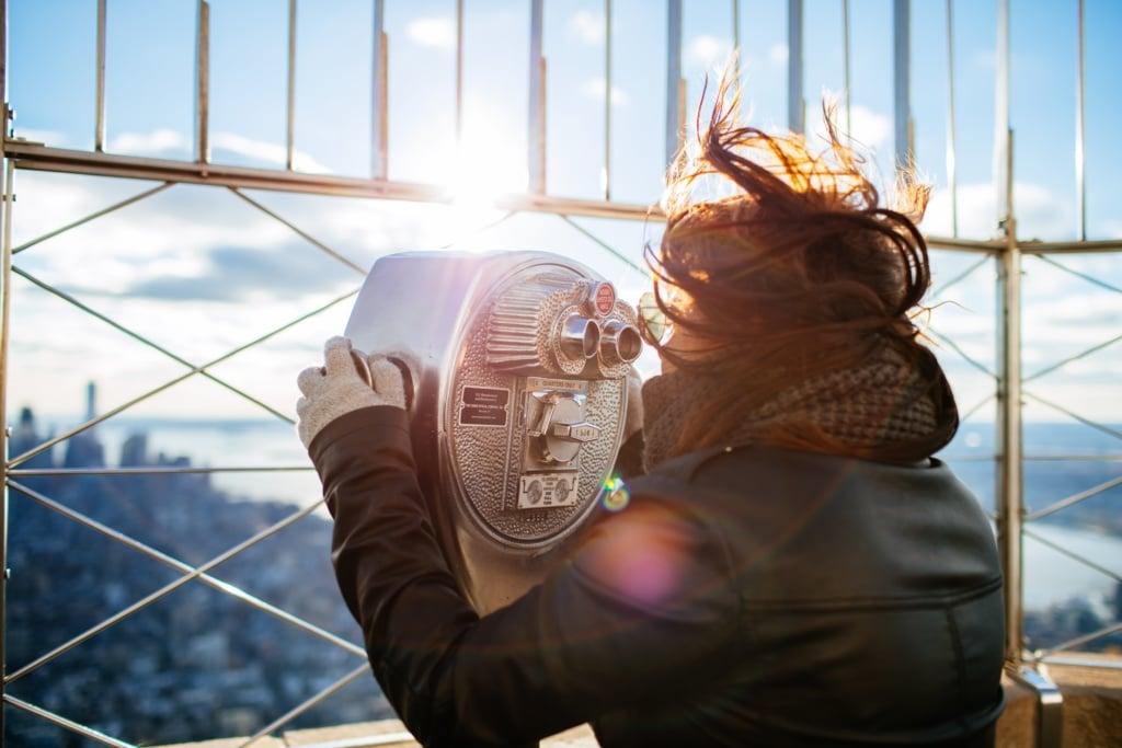 Frau auf dem Empire State Building versucht die Aussicht trotz Wind zu genießen