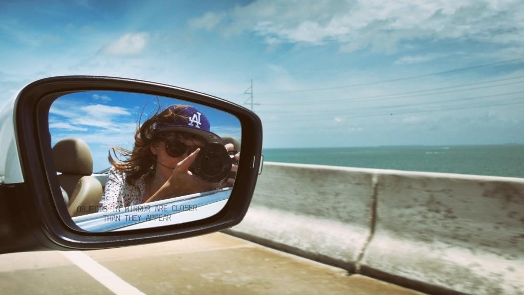 Frau im Rückspiegel mit kamera fährt in einem Cabrio über die Brücken der Florida Keys