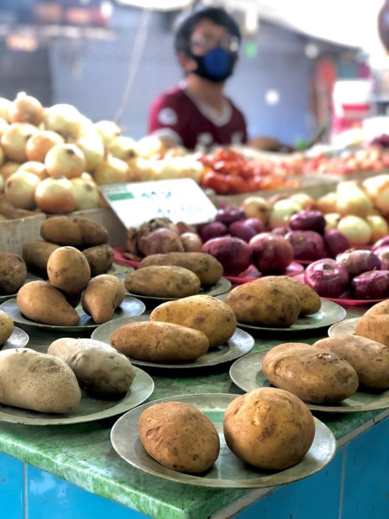 Marktverkäuferin mit Kartoffeln
