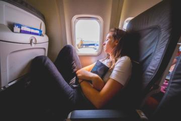 Frau schläft an Fensterplatz in Flugzeug