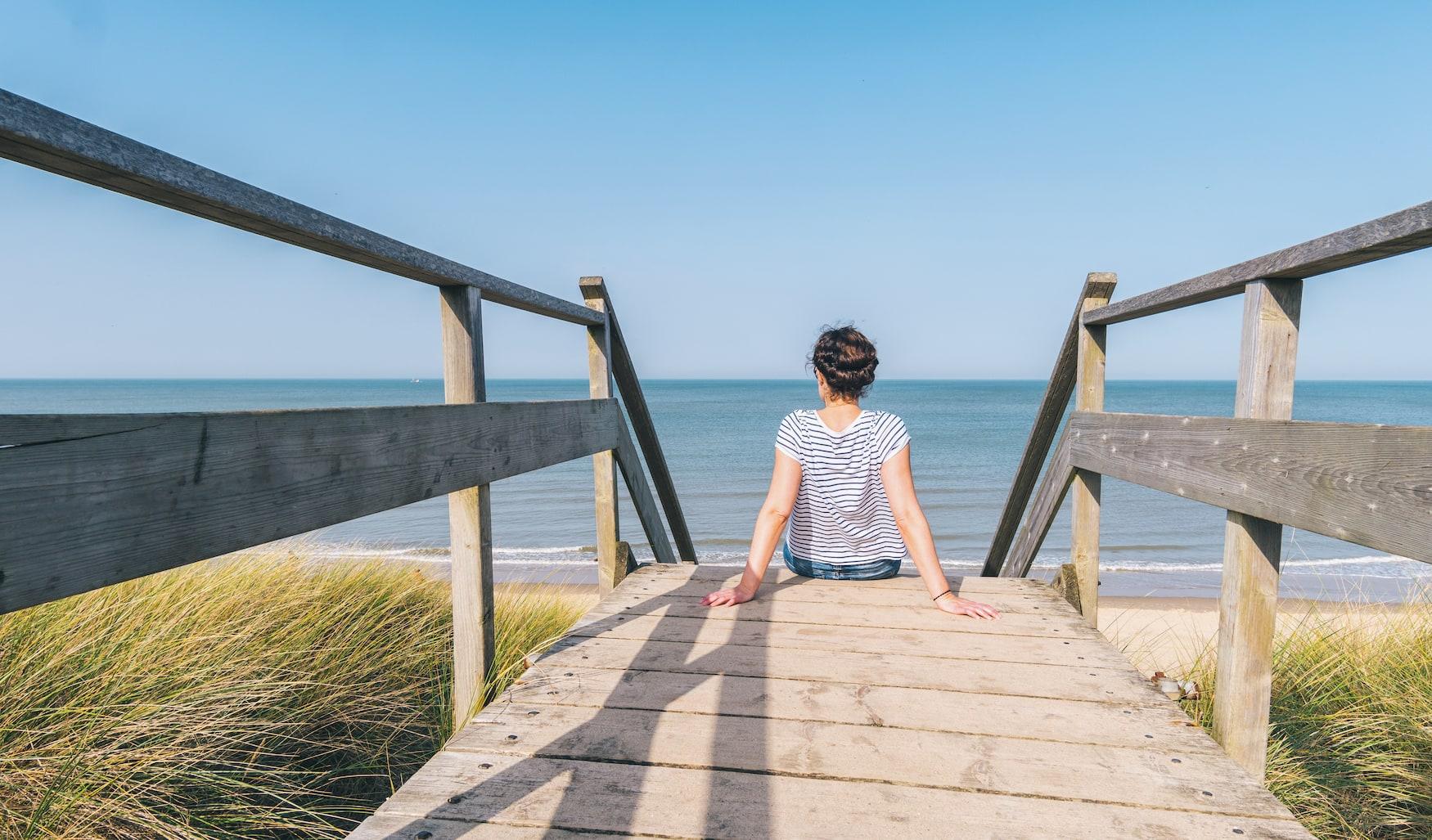 Frau sitzt auf einem Holzsteg an der Nordsee