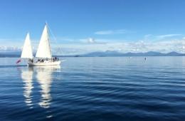 Segelboot auf seichtem Wasser vor Bergpanorama