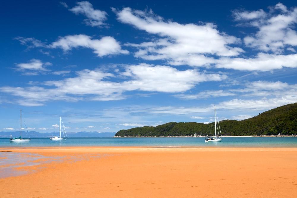 Feiner orangefarbener Strand mit türkisem Wasser un Segelbooten