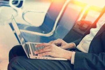 US-Laptop-Verbot: Geschäftsmann mit Laptop auf dem Schoß im Flughafen