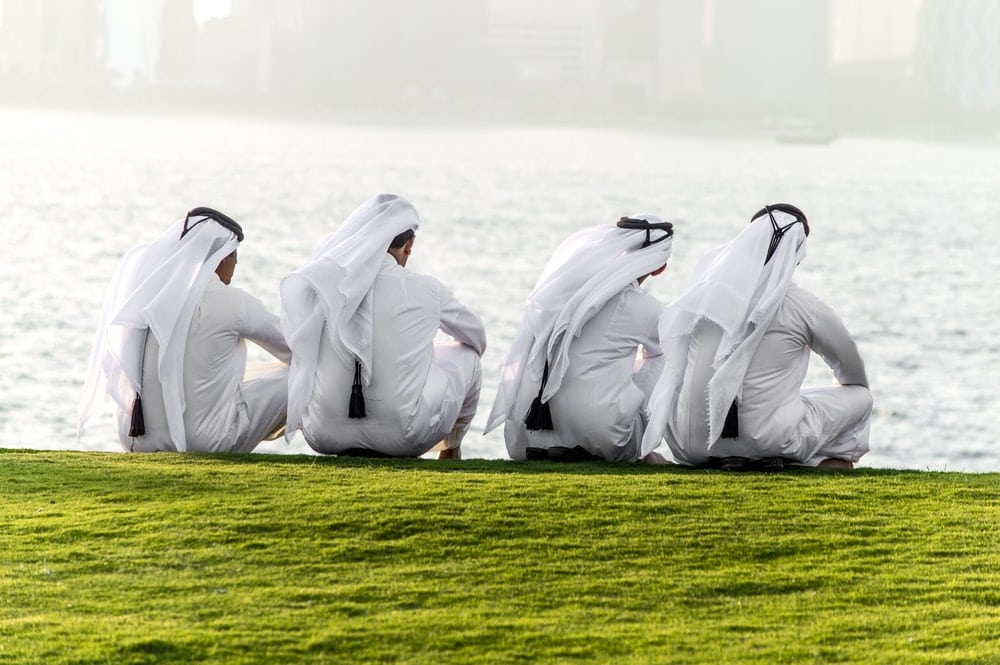 Männer in Katar, sitzend am Seeufer. Im Vordergrund eine grüne Wiese.