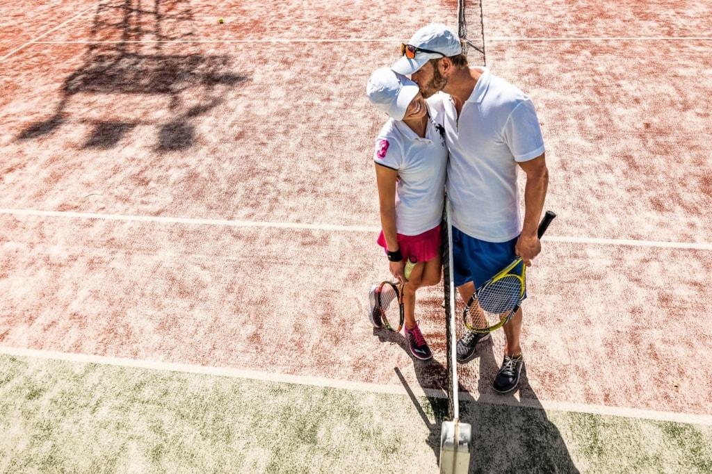 Mann küsst Frau auf Tennisplatz