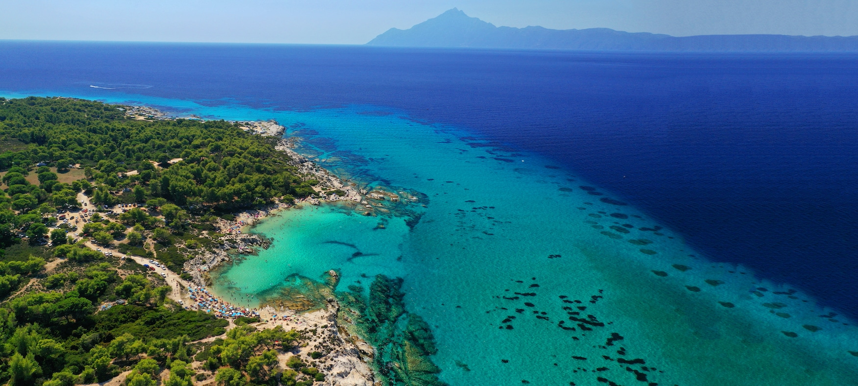 Die wunderschöne türkisfarbene Bucht und der Strand von Kavourotripes mit felsiger Meereslandschaft auf der Halbinsel Sithonia, Chalkidiki