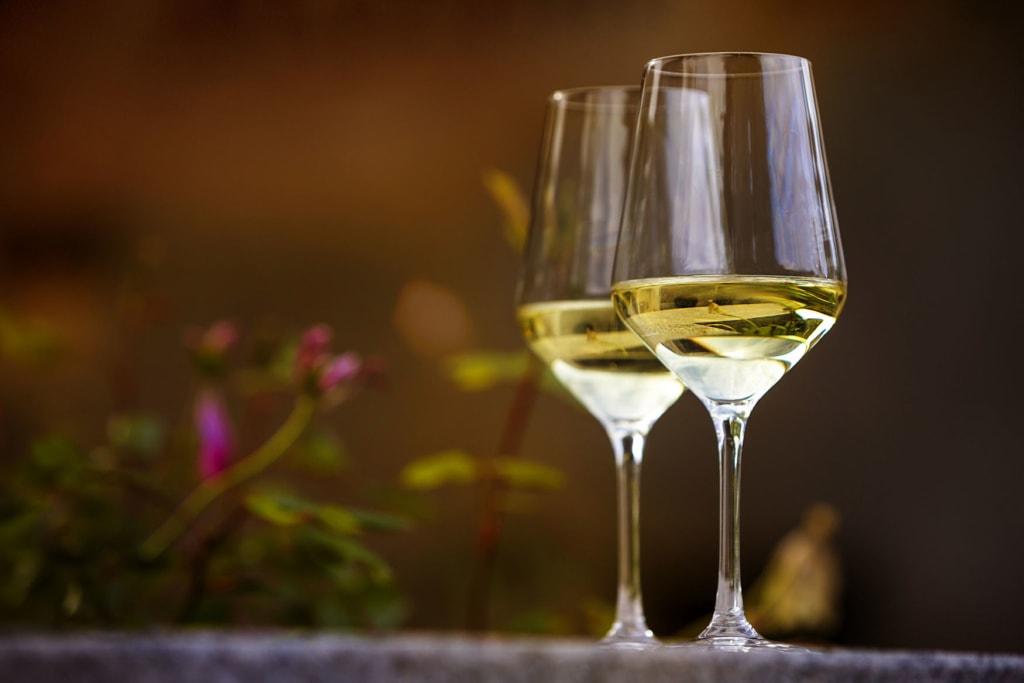 zwei Gläser Riesling auf einem Tischbeim weinwandernauf der Rieslingroute