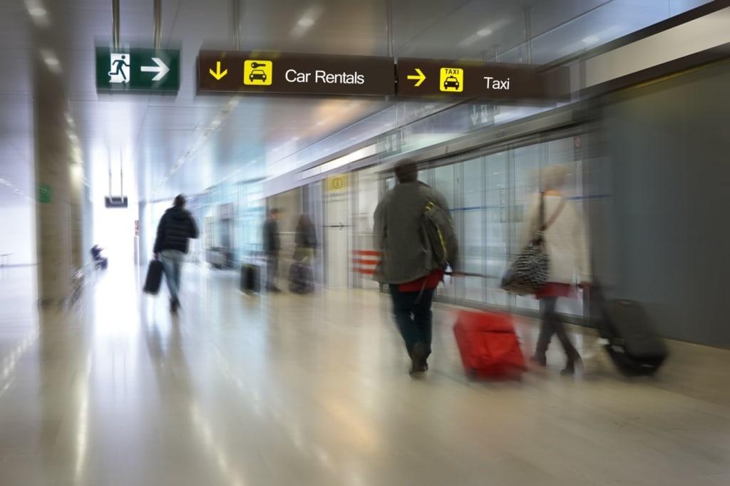 Flughafen-Passagiere auf dem Weg zur Mietwagen-Station