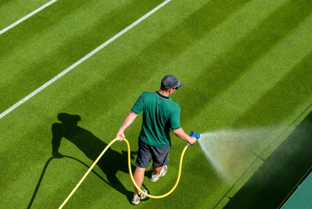 Wimbledon-Arbeiter mit Wasserschlauch auf Tennisplatz