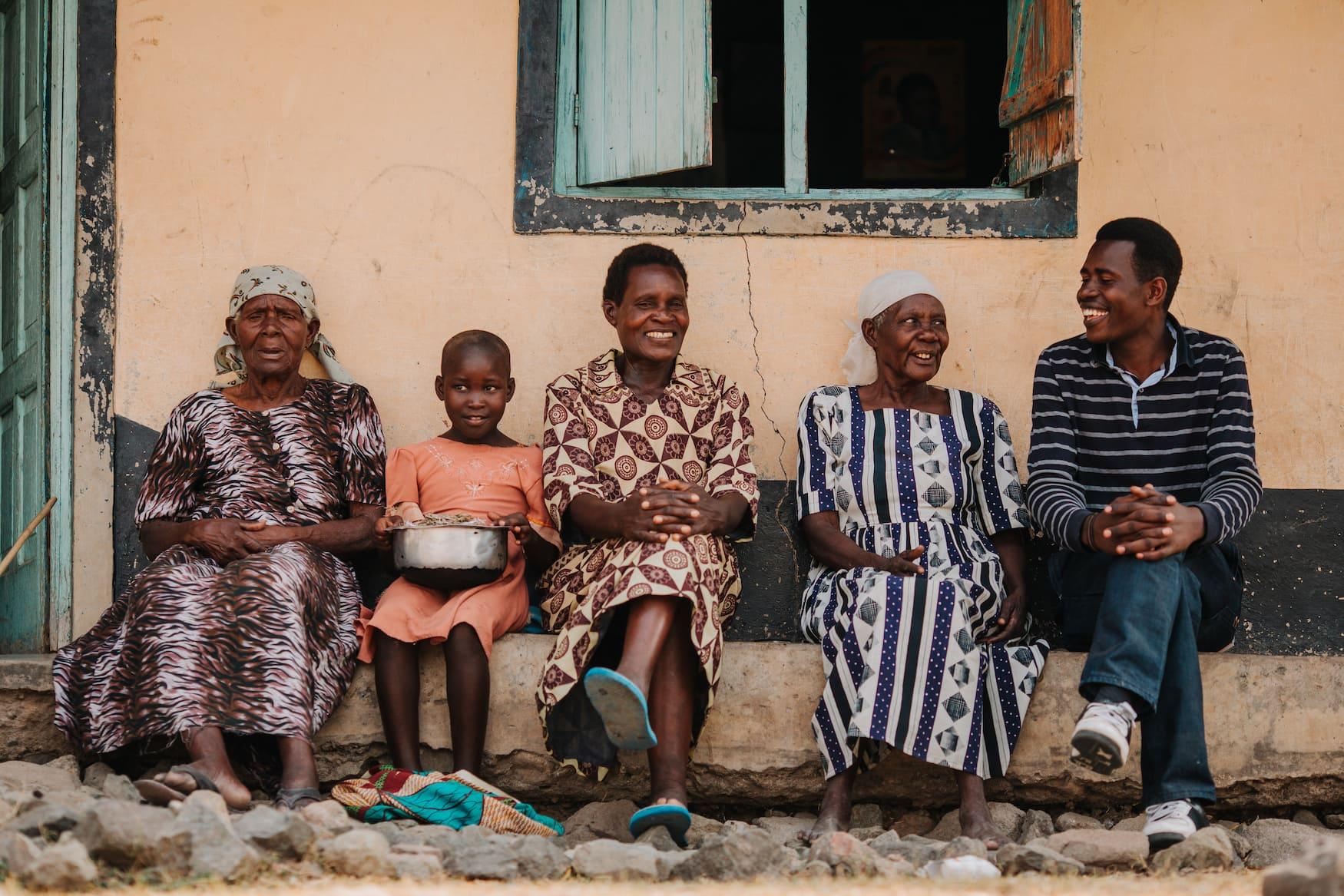 Einwohner in Kenia sitzen an Hauswand und warten
