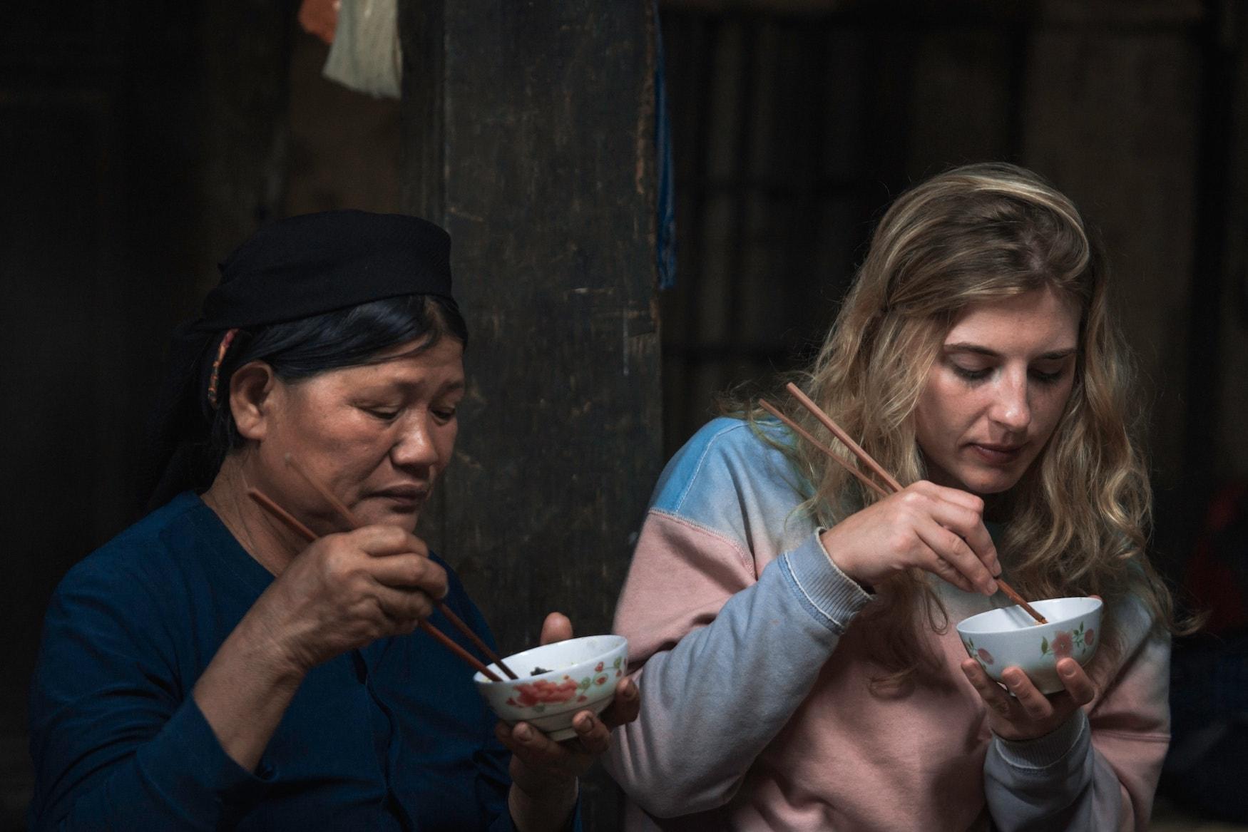 Zwei Frauen essen mit Stäbchen in Hongkong