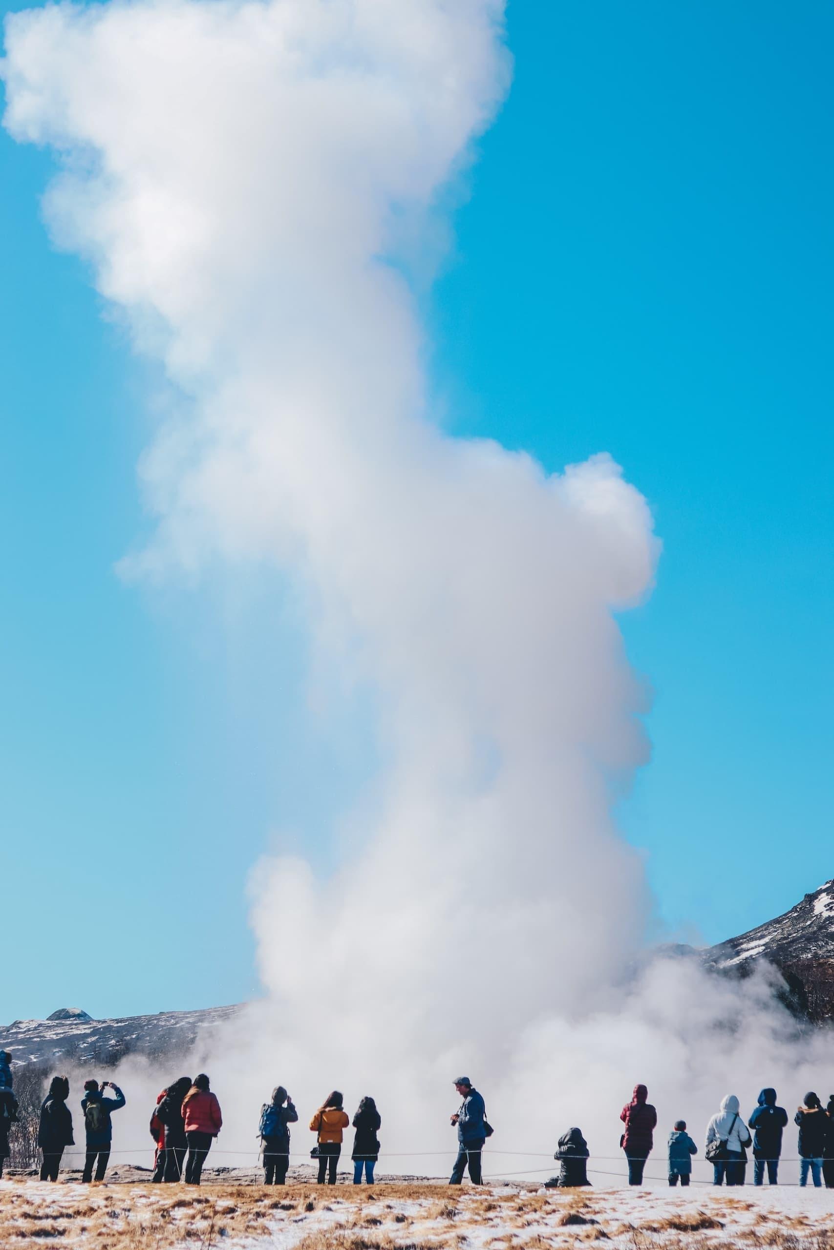 Menschen bestaunen ausbrechenden Geysir in Island