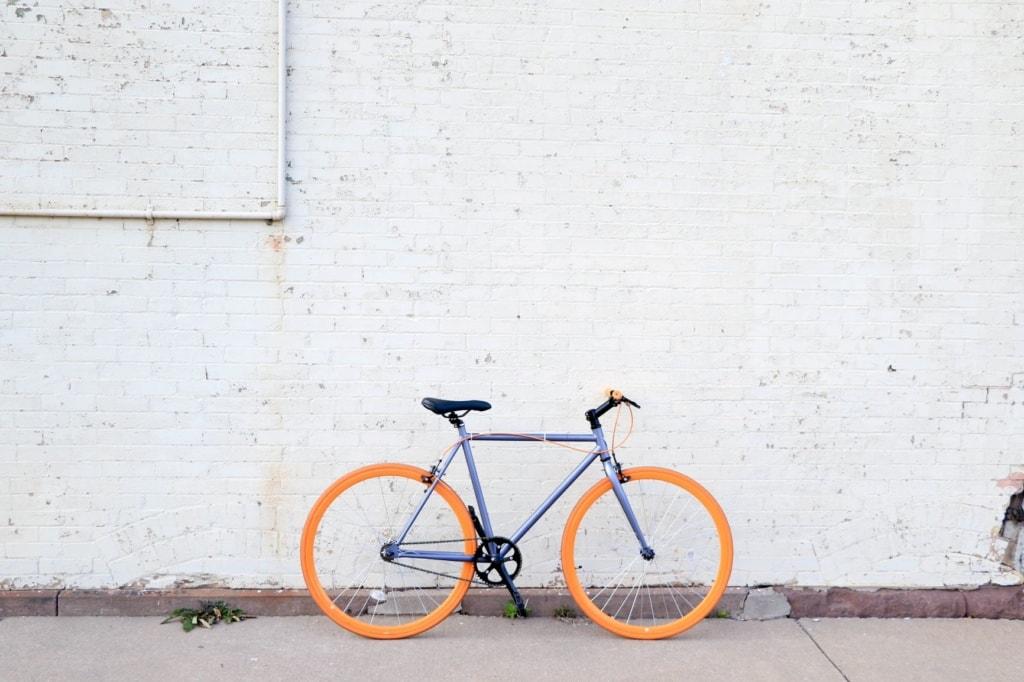 Fahrrad mit orange farbenen Reifen vor weißer Wand