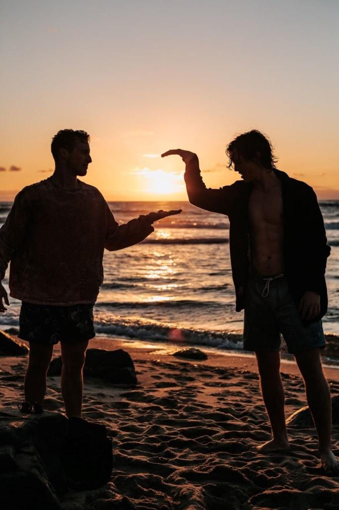 Zwei junge Männer schlagen sich am Strand in die Hand