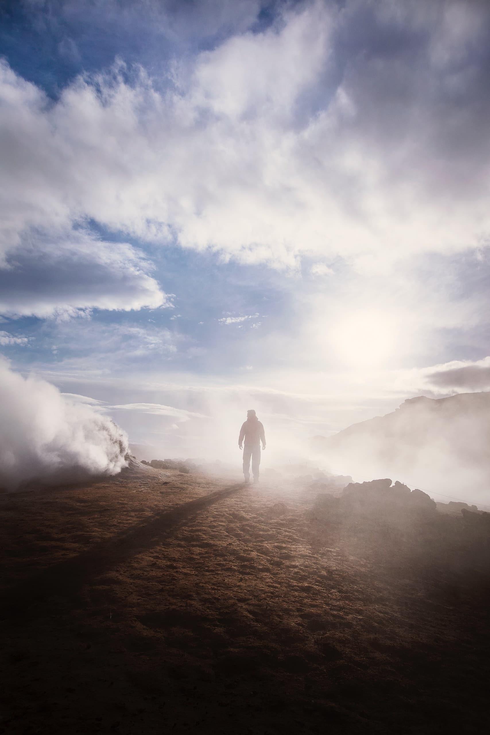 Mann wandert durch Qualm der Geysire