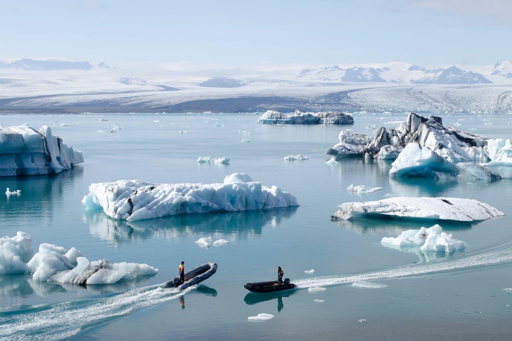 Kleine Boote fahren über See in Island. Überall liegen große Eisbrocken im Wasser.