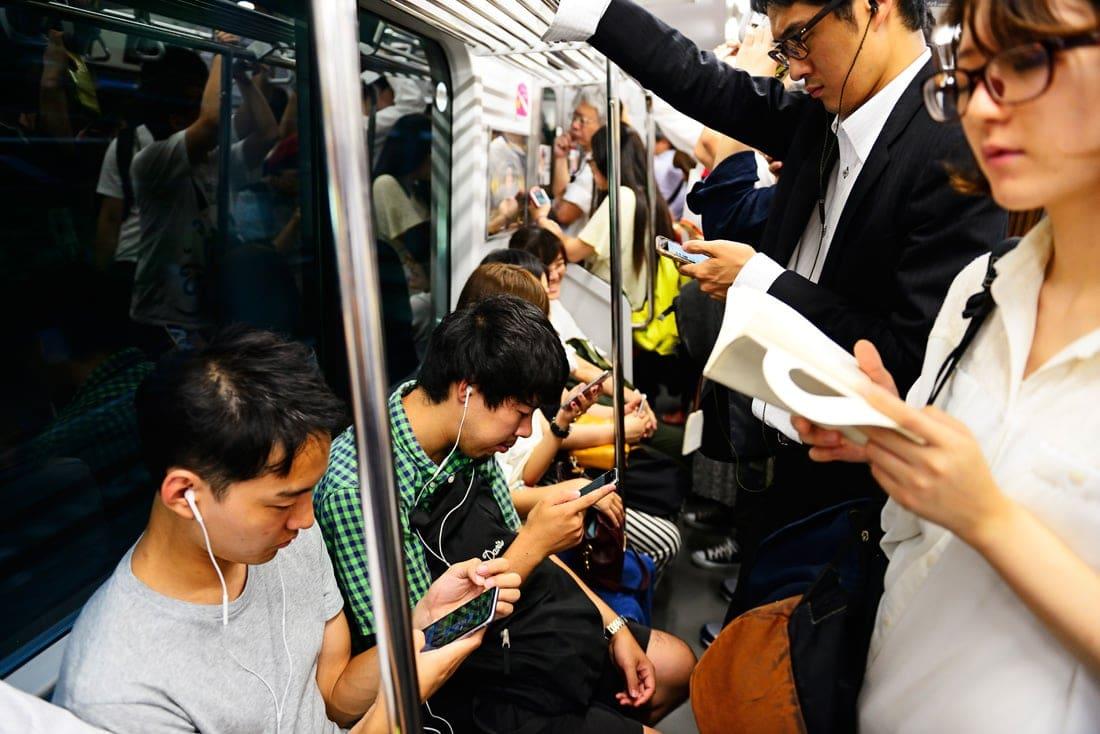 U-Bahn-Fahrer nutzen Smartphones in Tokio, Japan
