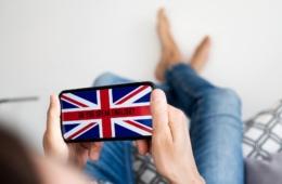 """Mann hält Handy in der hand mit der Aufschrift """"Do you speak english?"""" um einen auf das Englisch für den Urlaub vorzubereiten"""