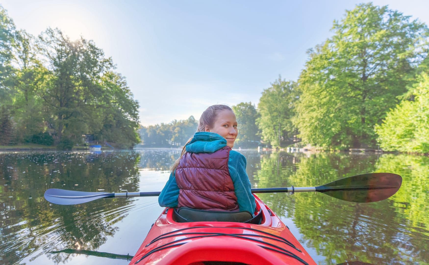 Wochenendausflüge in Deutschland: Junges Mädchen sitzt in Kayak auf Fluss in Sachsen