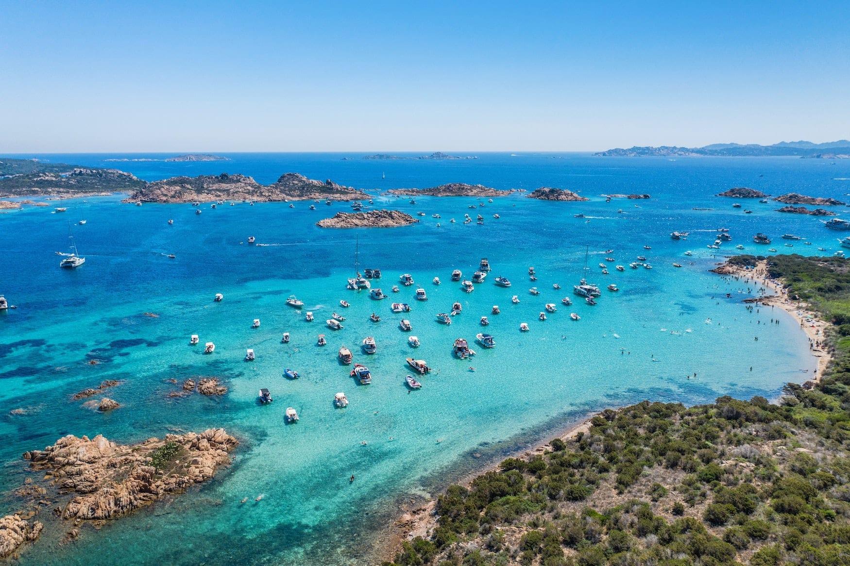 Boote liegen in Bucht auf Sardinien. Das türkisfarbene Wasser ist sicherlich eine der größten Sehenswürdigkeiten der Mittelmeerinsel