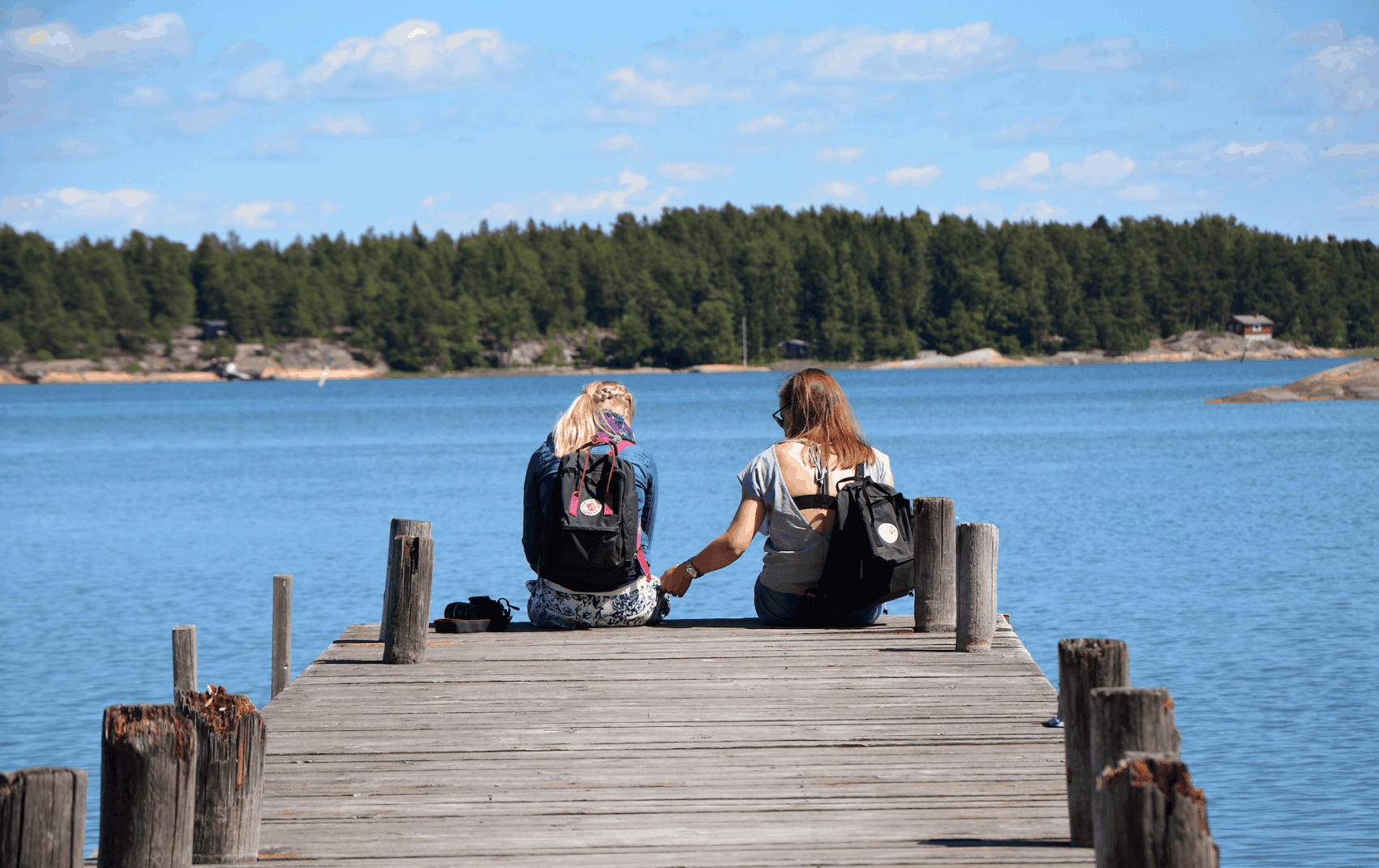 Finnland: Zwei jungen Frauen sitzen auf einem Steg